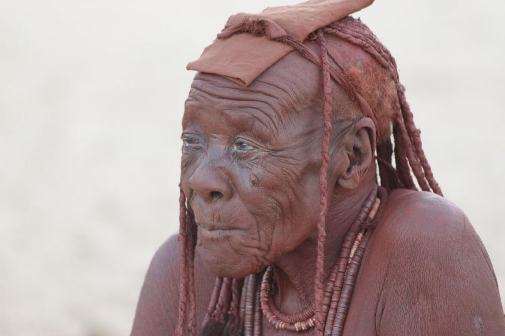 An elderly Himba lady sits contemplatively.
