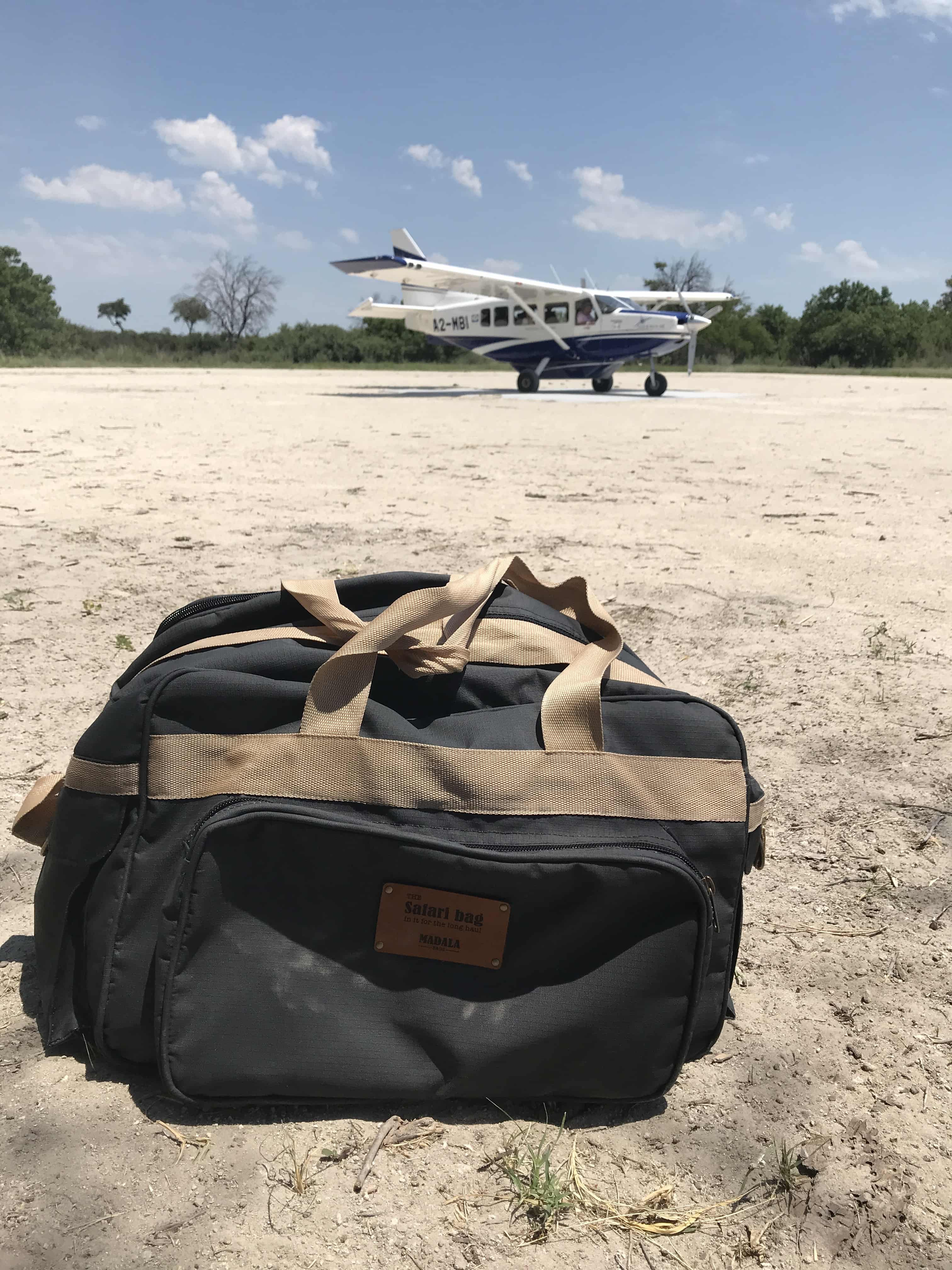 My Safari Bag on the sandy airstrip with the small plane we're about to board in the background.